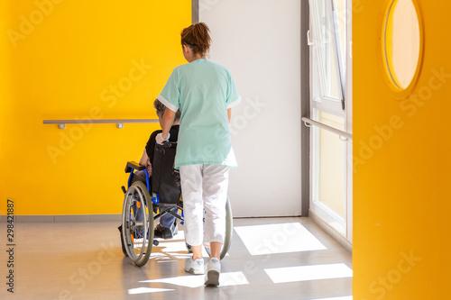 Soignante accompagne personne agée en fauteuil roulant Canvas Print