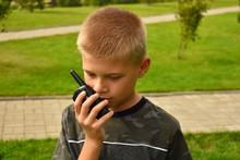 The Boy Is Talking On The Walkie-talkie. Children's Toy Walkie-talkie In Hand.