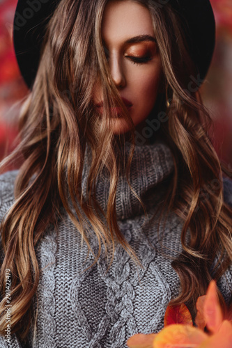 Fashion woman on a background of red and yellow autumn leaves Wall mural