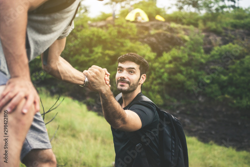 Fotografie, Obraz  Backpackers man getting help to friend climb at nature,Helping hand,Overcoming o