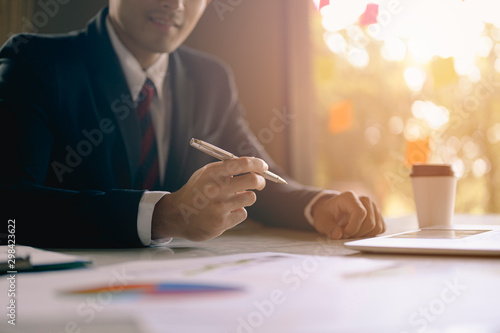 A young employee is writing a business plan on paper on a wooden table to propose a new project to the boss at the office Wallpaper Mural