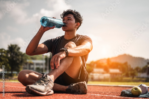 The young man wore all parts of his body and drink water to prepare for jogging on the running track around the football field Fototapete