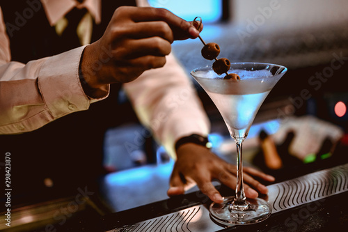 The young bartender is making a cocktail and decorating it in a martini cocktail glass for beautiful at a nightclub bar Canvas Print