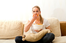 Woman Eating Chips And Watching Tv. She Is Stressed And She Eating Junk Food.