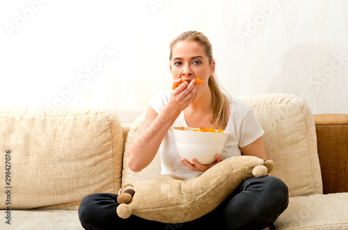 Fototapeta Woman eating chips and watching tv. She is stressed and she eating junk food. obraz