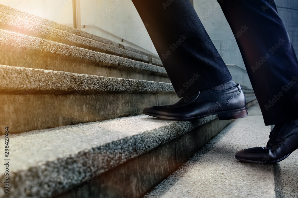 Fototapeta Motivation and challenging Career Concept. Steps Forward into a Success. Low Section of Businessman Walking Up on Staircase. Male in Black Formal Dress