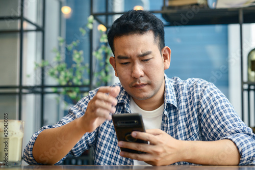 Foto  Depressed Asian man using smartphone in cafe, lifetyle concept.