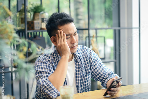 Depressed Asian man using smartphone in cafe, lifetyle concept.