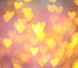 canvas print picture Blurred view of gold heart shaped lights on pink background
