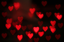 Blurred View Of Red Heart Shaped Lights On Black Background