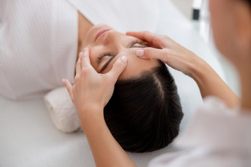Obraz na płótnie Canvas Masseuse hands massaging face of young woman