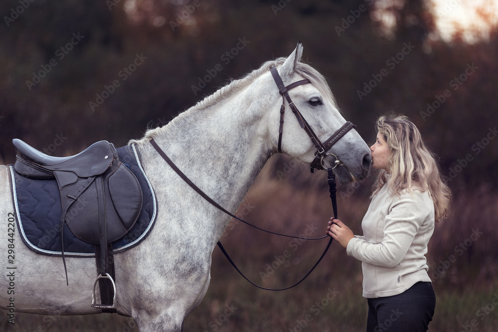 Fototapeta Beautiful girl posing with a purebred arabian horse outdoors.