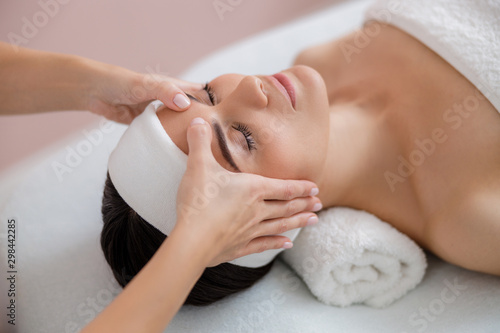 Relaxed young woman having therapeutic face massage - 298442285