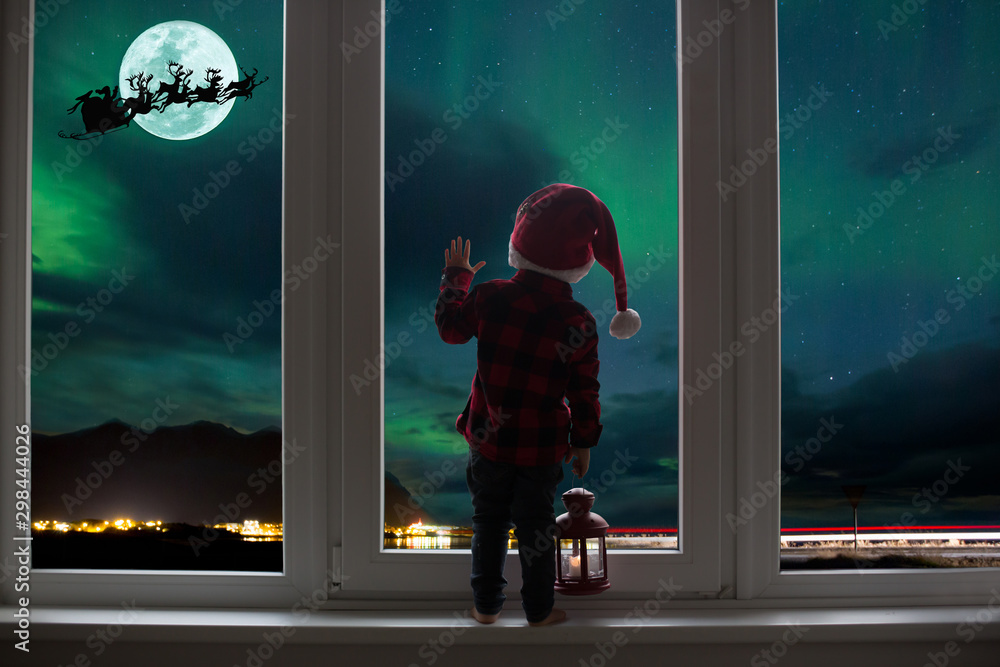Fototapeta Toddler child standing in front of a big french doors, leaning against it looking out, holding lantern