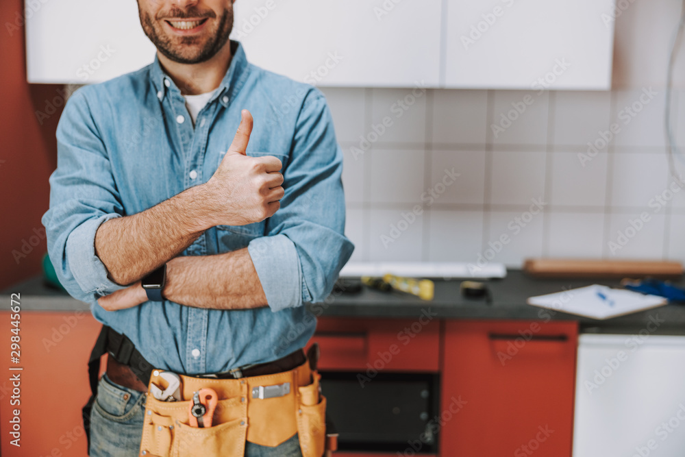 Fototapety, obrazy: Smiling repairman staying with tool belt at home