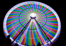 Ferris Wheel At Night With Colorful Blur. Holiday Fun On Carousel In Park. Slow Montion.