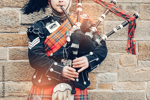 Canvastavla EDINBURGH, SCOTLAND, 24 March 2018 , Scottish bagpiper dressed in traditional red and black tartan dress stand before stone wall