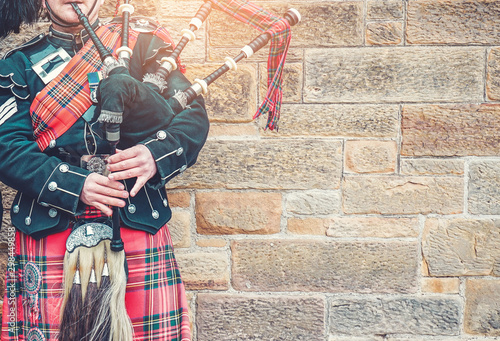 Fotografia EDINBURGH, SCOTLAND, 24 March 2018 , Scottish bagpiper dressed in traditional red and black tartan dress stand before stone wall