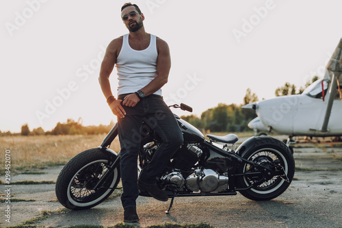 Adult man holding hand in pocket near motorbike Tablou Canvas