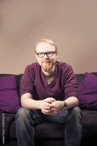 Attentive Caucasian Male Sitting on Sofa Looking at Camera Wallpaper Mural