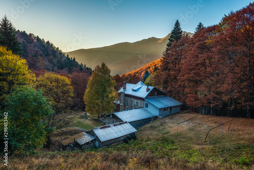 Vasil Levski mountain hut in Old mountain (Stara planina), Central Balkan national park, Old river reserve, Bulgaria. Autumn landscape, colorful forest with clear blue sky during sunset