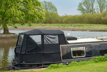 Moored Narrow Boat Seen On An Inland Waterway During Late Spring.  One Of A Number Of Narrow Boats Used For Hire And Also Private Owners.