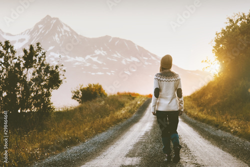 Fototapeta Woman walking alone on gravel road in mountains Travel lifestyle adventure vacations escape outdoor obraz
