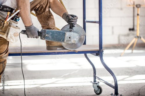 The industrial Builder works with a professional angle grinder to cut bricks and build interior walls Canvas Print