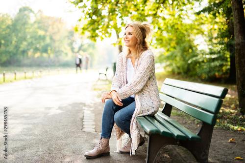 Foto Attraktive Frau im mittleren Alter sitzt im Park auf einer Bank