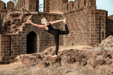 Girl Doing Yoga On The Wall Of An Ancient Fort In India. Healthy Lifestyle With Yoga Beautiful Body And Health Through Exerciseasana, Balance, Beach, Beautiful, Body, Calm, Class, Concentration, Doing