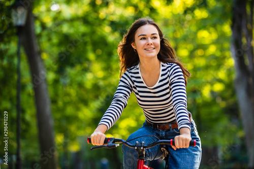Urban biking - woman riding bike in city park Fototapeta