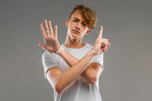 A Portrait Of Young Caucasian Man With Short Red Curly Hair In White T-shirt Show A Six Fingers Isolated On A Grey Background
