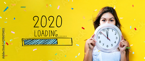 Loading new year 2020 with young woman holding a clock showing nearly 12 Tablou Canvas