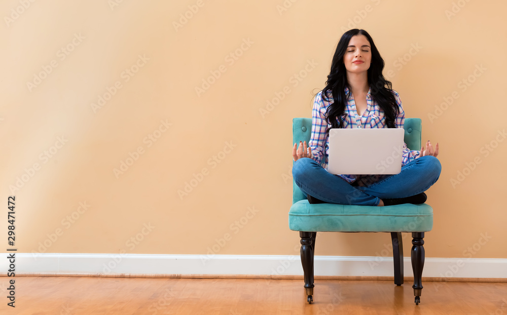 Fototapety, obrazy: Young woman with laptop in a meditation pose pose sitting in a chair