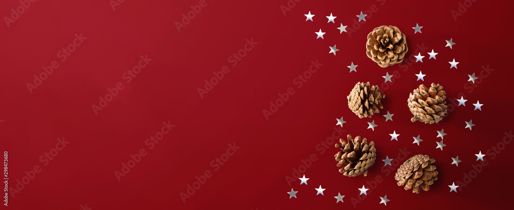 Fototapeta Christmas pinecones with star confetti - flat lay