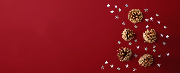 Fototapeta na wymiar Christmas pinecones with star confetti - flat lay