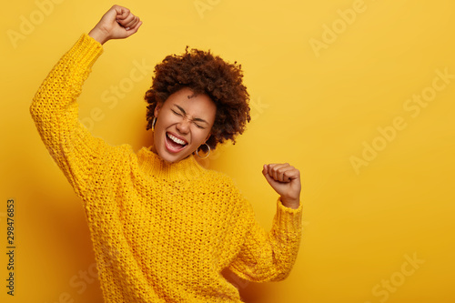 Curly haired girl in winter yellow sweater dances with arms spreading in air, enjoys music, has overjoyed face expression, being on party, enjoys concert poses indoor. People, fun, emotions, happiness - 298476853