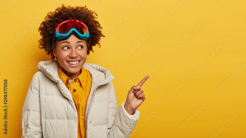 Fototapety, obrazy: Happy female snowboarder wears skiing mask, looks away and points index finger on blank space, rests in mountains, dressed in warm white jacket, promots something on copy space. Active lifestyle