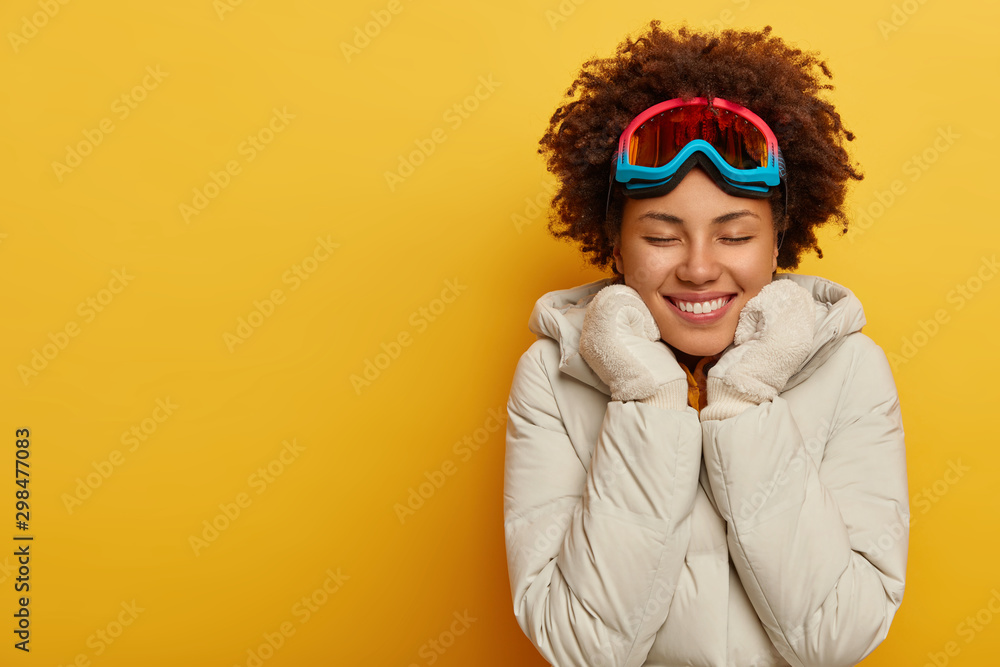 Fototapety, obrazy: Sport, ski resort and snowboarding concept. Happy Afro woman wears ski mask, warm knitted mittens and coat, has awesome winter holidays, enjoys outdoor activities. Glad female in snowboard wear