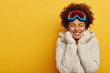 Sport, ski resort and snowboarding concept. Happy Afro woman wears ski mask, warm knitted mittens and coat, has awesome winter holidays, enjoys outdoor activities. Glad female in snowboard wear