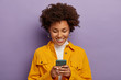 canvas print picture - Photo of glad female blogger types text content for web publication, focused in smartphone, wears yellow shirt, checks received notification, smiles gently, isolated over purple studio wall.