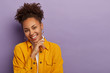 canvas print picture - Studio shot of charming pleased young woman with curly combed pony tail, touches chin gently, smiles gladfully, enjoys pleasant conversation, wears fashionable yellow jacket, round big earrings