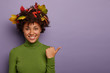 canvas print picture - Happy woman with curly hair decorated by autumnal leaves, poses indoor, points thumb aside, dressed in green casual turtleneck, gives suggestion, isolated over purple background, smiles broadly