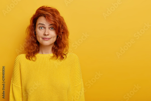 Valokuvatapetti Portrait of young ginger woman has natural beauty, dressed in yellow knitted jumper, dimples at cheeks looks at camera with eyebrows raised, likes bright clothes