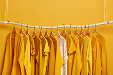 Set Of Bright Yellow Clothes And One White Sweater On Hangers. Collection Of Womens Attires To Wear. Variety Of Outfits For Warm And Hot Weather. Wadrobe Closet. Fashion, Shopping And Consumerism