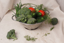 Green Onions, Broccoli, Dill, Tomatoes And Cucumbers In An Iron Colander On A Fabric Background