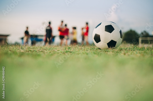 Photo Action sport outdoors of a group of kids having fun playing soccer football for exercise and recreation at the green grass field in community rural area under the twilight sunset sky
