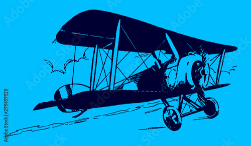 Slightly ascending historical biplane in front of a cloudy sky on a blue background Wallpaper Mural