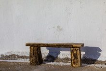Rustic Wooden Bench And Its Shadow On The Wall