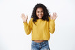 Happy pretty african american girl with curly hair showing excitement and happiness, greeting friends, waving raised palms hello, hi gesture, finally can wear new yellow sweater autumn chilly day
